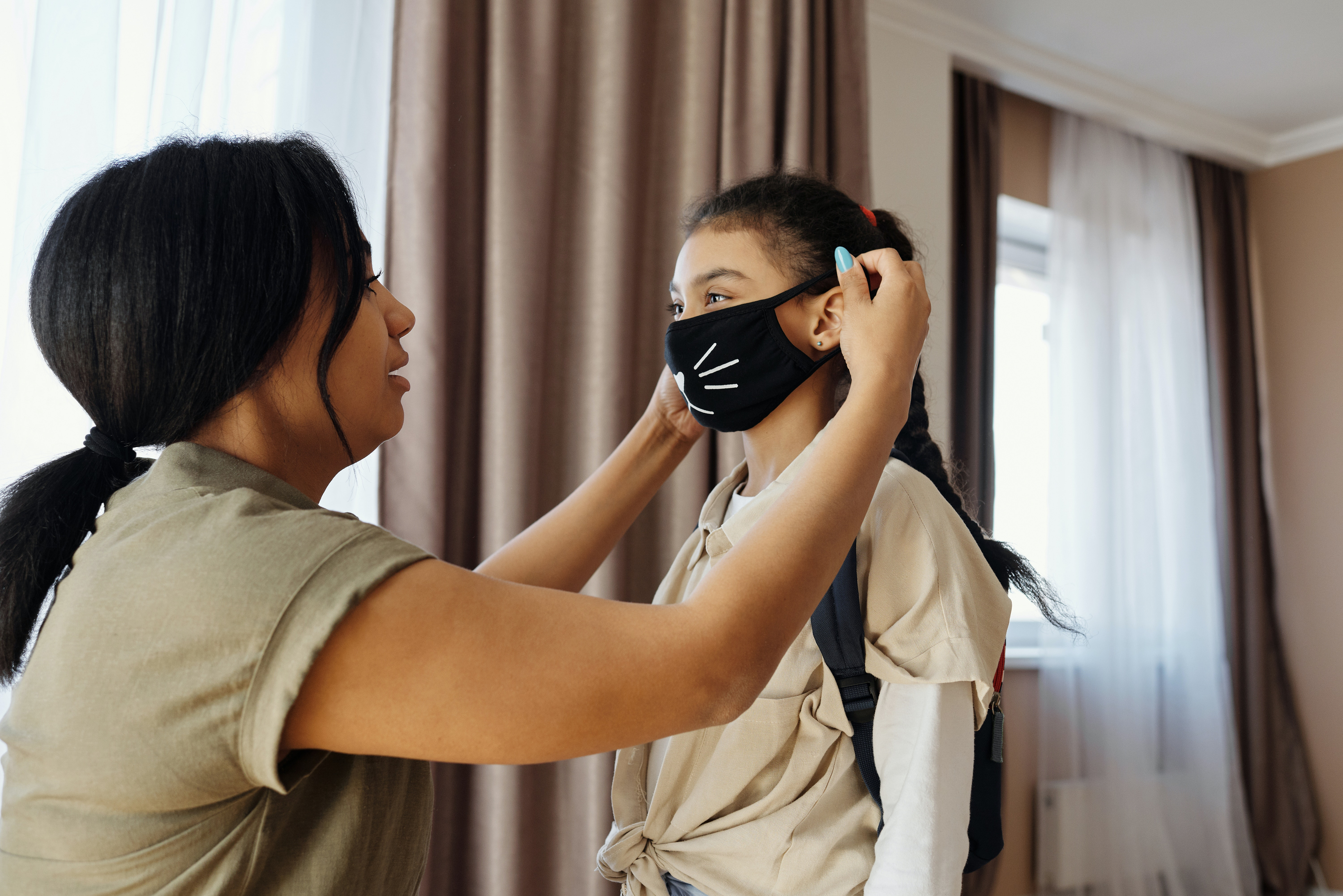 Parent placing mask on student for school